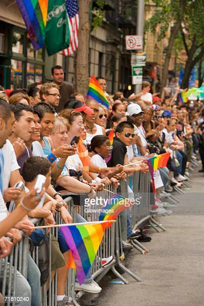 Large group of people holding gay pride flags and standing by a railing