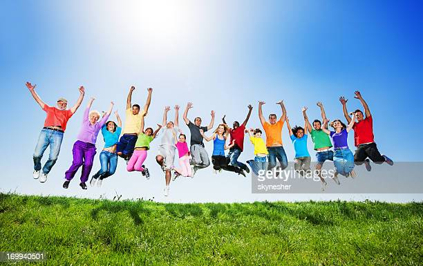 Large group of people jumping against the clear sky.