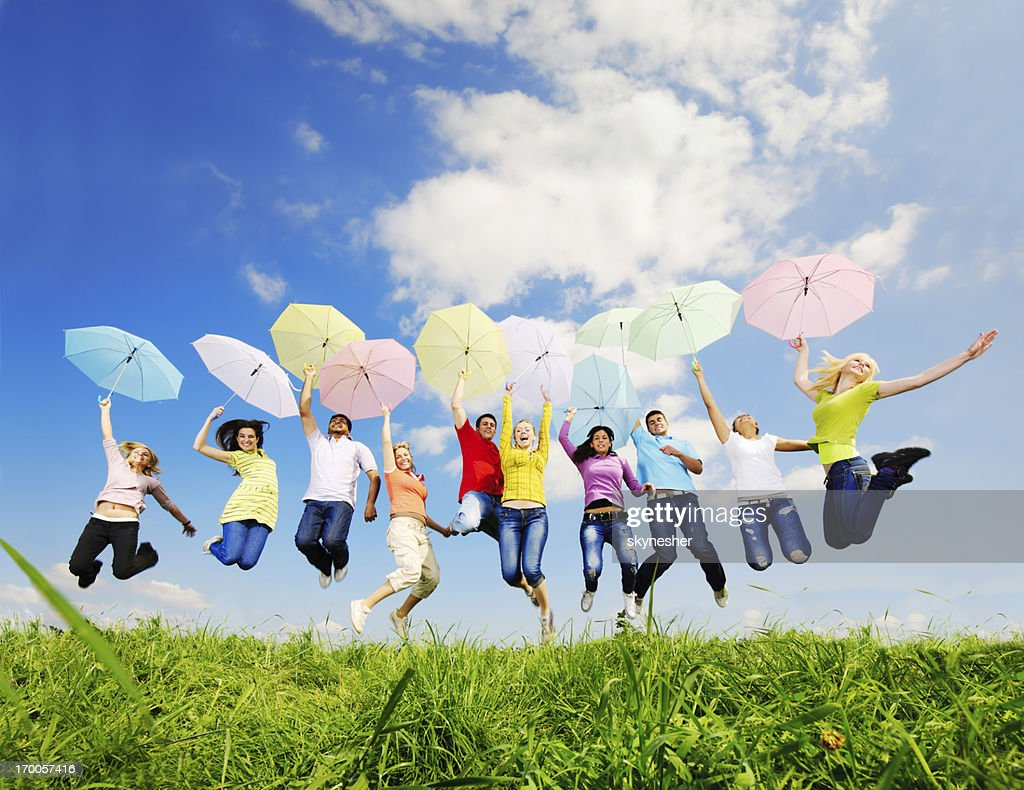 Large group of people jumping with umbrellas. : Stock Photo