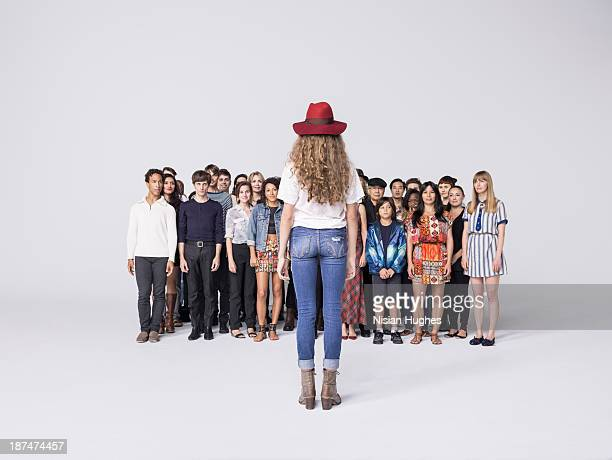 Large Group of people look at woman in front