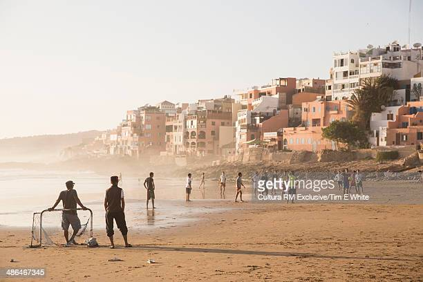 Large group of people playing football on beach, Taghazout, Morocco
