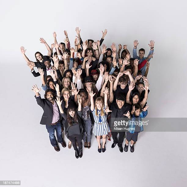 Large group of people together with arms up