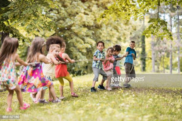 Large group of playful kids playing tug-of-war in nature.