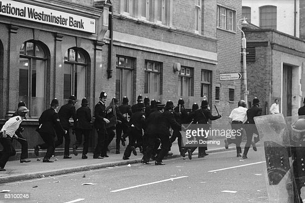 A large group of policemen outside a National Westminster Bank during the Brixton Riot of 11th April 1981