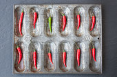 Large group of red chillies and one green chilli ordered in baking tin