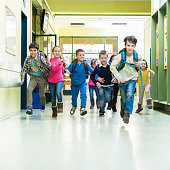 Large group of school children running in the hall.