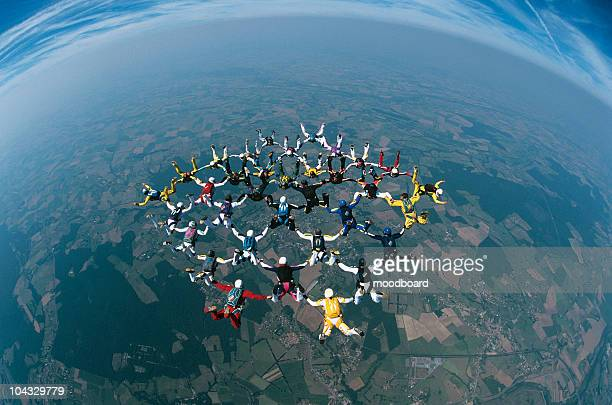 Large group of skydivers flying in formation over earth, elevated view