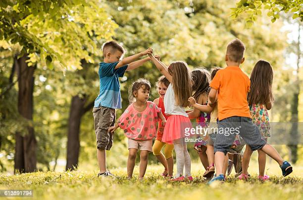 Large group of small children having fun while playing outdoors.
