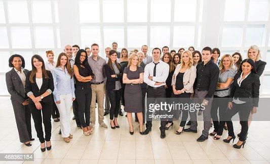Sonriente gran grupo de gente de negocios mirando a la cámara.