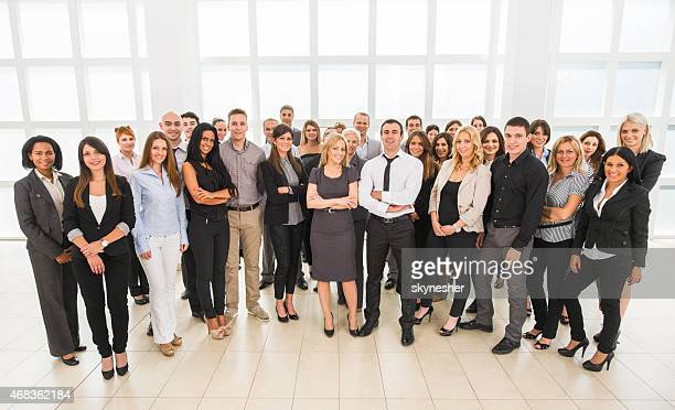 Large group of smiling business people looking at the camera.