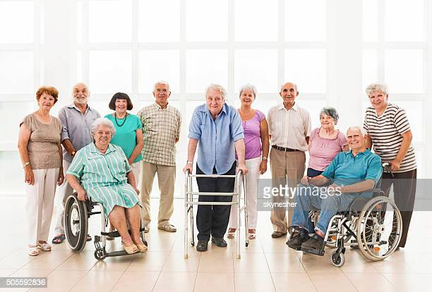 Grupo grande de ancianos sonriente mirando a la cámara.