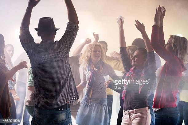 Large group of smiling young people disco dancing.