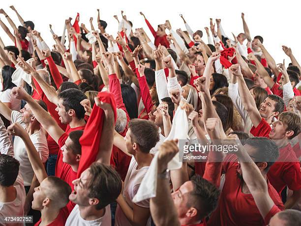 Large group of sport fans cheering with their arms raised.