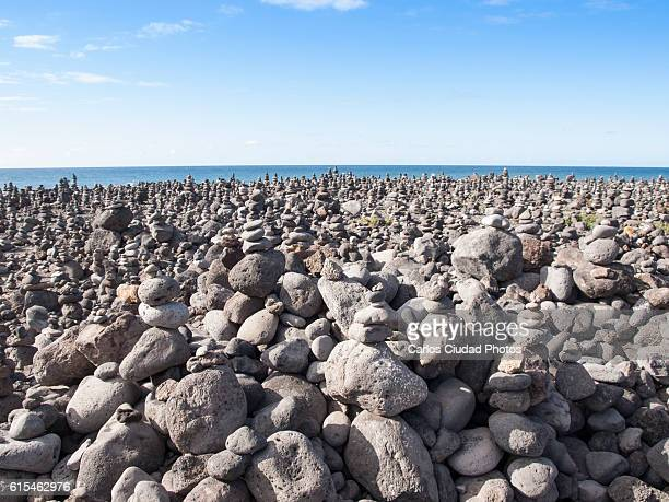 Large group of stacked rocks against  blue sky