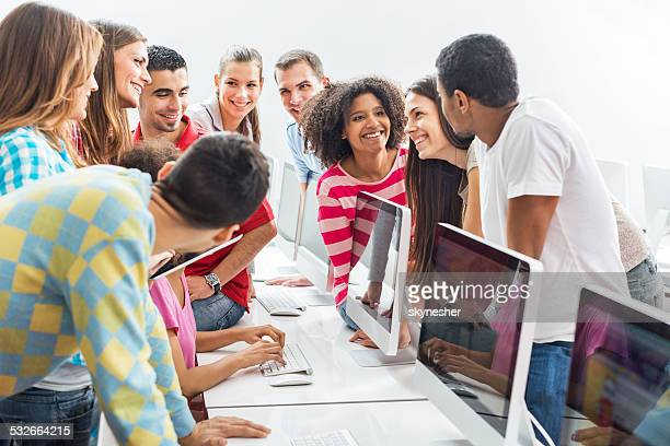 Large group of students talking at computer lab.