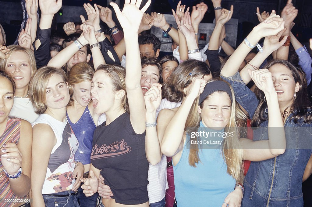 Large group of teenagers dancing at club, front view : Stock Photo