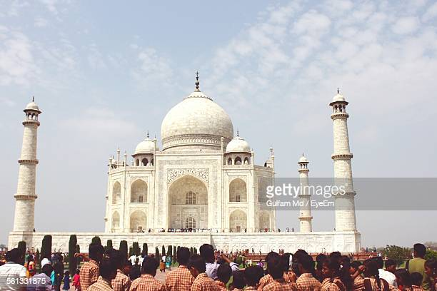 Large Group Of Tourist Looking At Facade Of Taj Mahal Against Sky