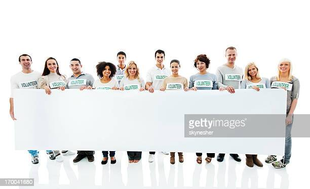 Large group of volunteers holding a big white board.