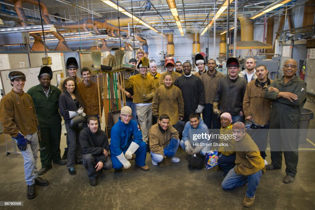 Large group of welders posing in foundry : Stock Photo