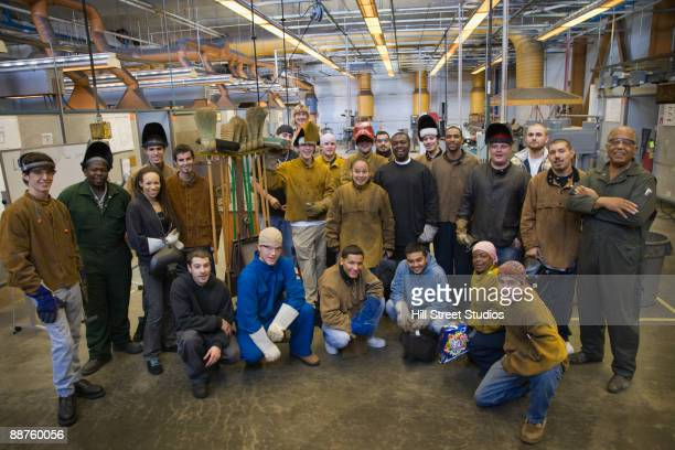 Large group of welders posing in foundry