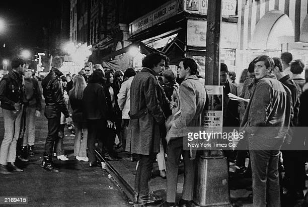 A large group of young people stand gathered at the intersection of MacDougal and West 3rd Street in Greenwich Village New York City April 22 1967