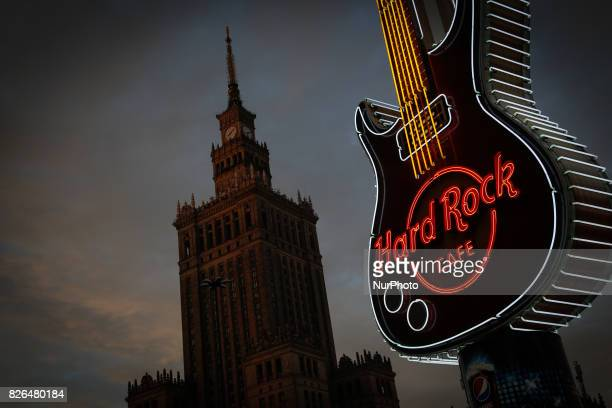 A large guitar effigy decorated in neon lighting advertising the nearby Hard Rock cafe can be seen with the Palace of Science and Culture landmark in...