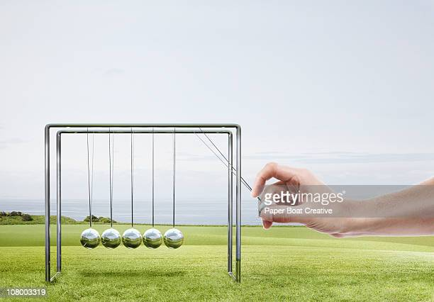 Large hand swinging a newton's cradle
