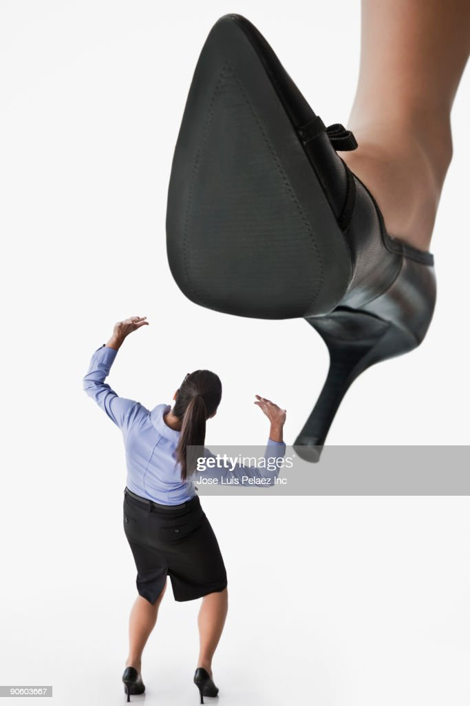 Large high heel looming over businesswoman : Stock Photo