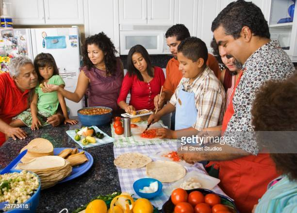 Large Hispanic family in kitchen preparing food