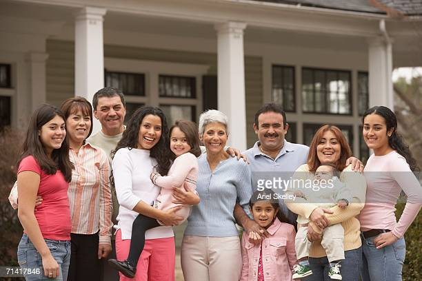 Large Hispanic family standing in front of house