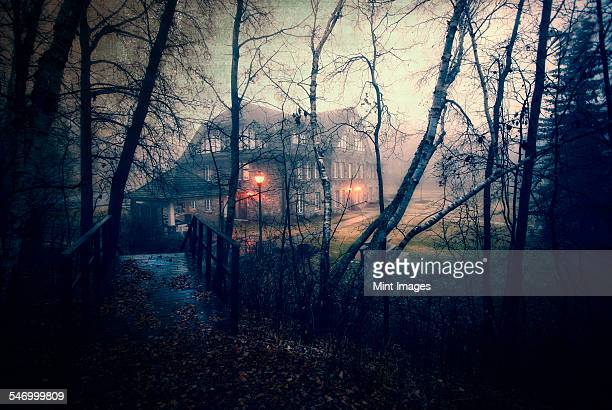 A large house at dusk with lights glowing. Woodland. A footbridge.