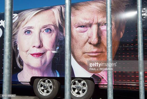 TOPSHOT Large images of Democratic nominee Hillary Clinton and Republican nominee Donald Trump are seen on a CNN vehicle behind asecurity fence on...