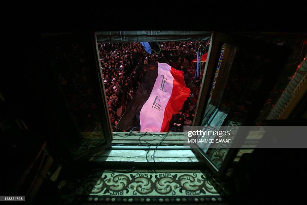 A large Iraqi flag is seen as Shiite Muslim pilgrims take part in the Arbaeen religious rituals which marks the 40th day after Ashura commemorating the seventh century killing of Prophet Mohammed's grandson, Imam Hussein, in the shrine city of Karbala, southwest of Iraq's capital Baghdad, on January 2, 2013.
