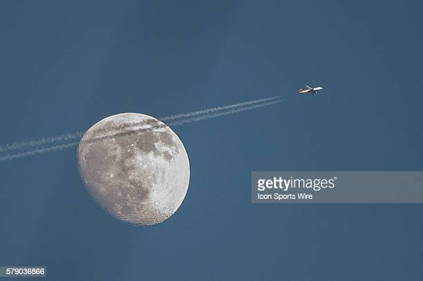 A large jet plane is seen in front of the moon from Coors Field during a regular season Major League Baseball game between the Atlanta Braves and the...