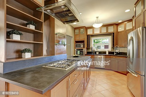 Large kitchen room interior with brown cabinets and steel appliances : ストックフォト