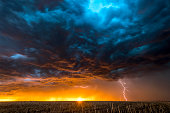 A nighttime, tornadic mezocyclone lightning storm shoots bolt of electricity to the ground and lights up the field and dirt road in Tornado Alley.  A large lightning strike at dusk in an open plain fr