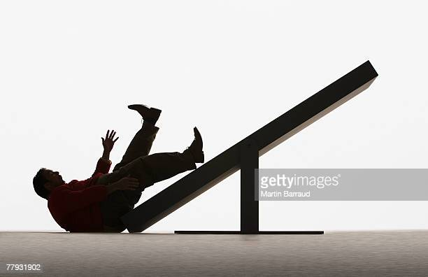 Large man falling off end of plank
