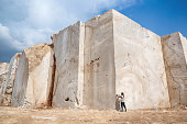 Marble rock block sections in a quarry. Sculptor is checking the quality of stone.