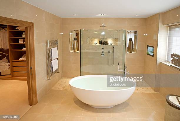 Large marbled tiled bathroom with oval tub and glass shower