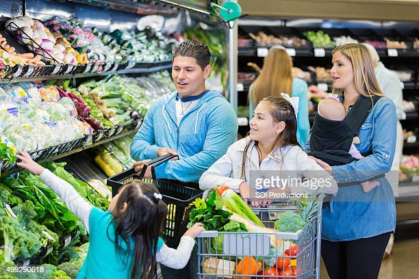 Large mixed race family shopping for groceries together at supermarket
