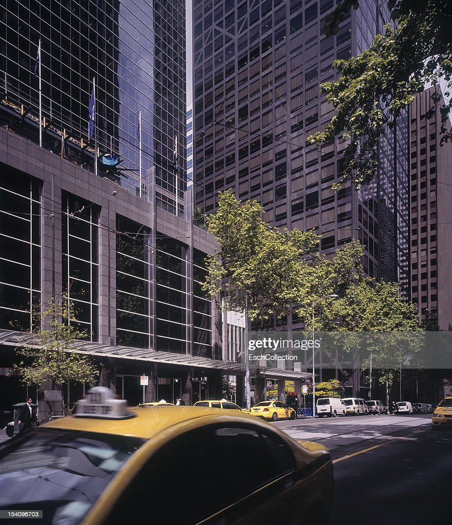 Large modern office buildings and yellow cabs : Stock Photo