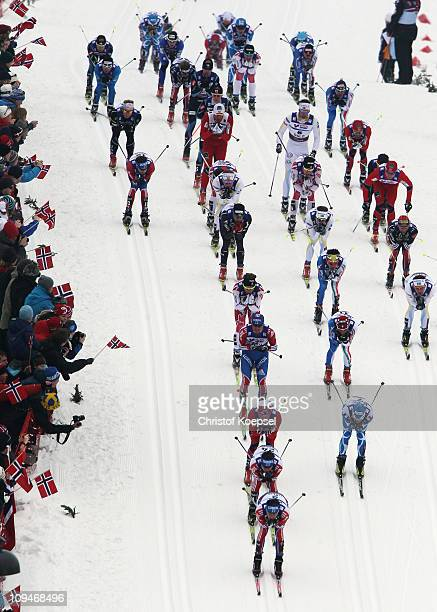 A large pack of athletes are cheered on by the fans in the Men's Cross Country 30km Pursuit race during the FIS Nordic World Ski Championships at...