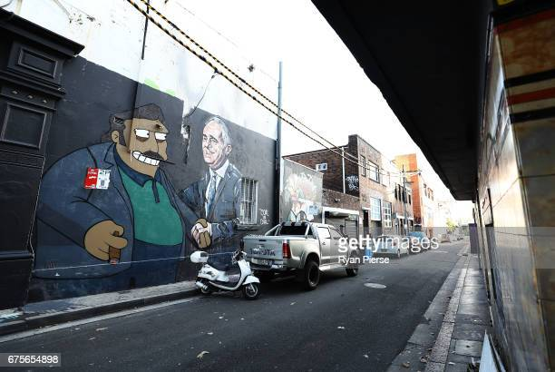 A large painted mural on the side of a building in Chippendale depicts Prime Minister Malcolm Turnbull shaking hands with The Simpsons character 'Fat...