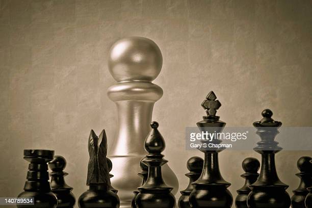 Large pawn and small chess pieces