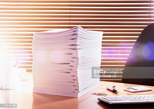 Large pile of documents on office desk.