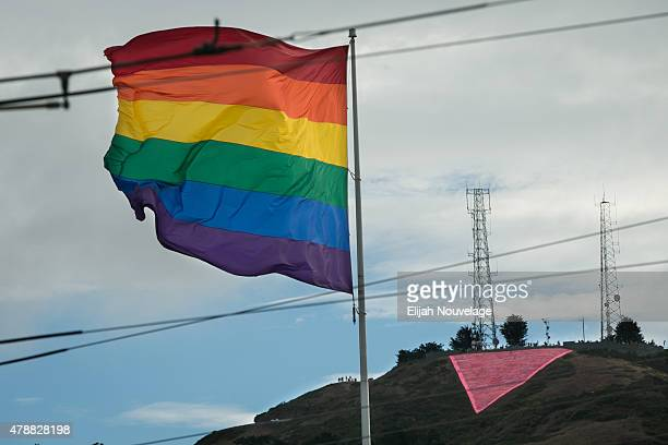 A large pink triangle is seen behind a rainbow flag during a gay pride celebration on June 27 2015 in San Francisco California The Supreme Court...