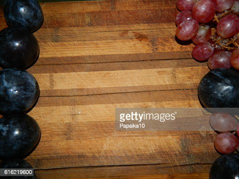 Large  plums and grapes on the sides of the wooden board : Stock Photo