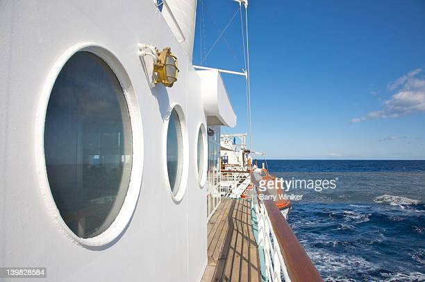 Large portholes, deck, shadows, rail, Mediterranean Sea and sky from motorized sail ship Wind Spirit of Windstar Cruises