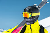 A large portrait of a skier in a protective helmet and glasses is a mask and scarf with skis on his shoulder in the snow-capped mountains of the Caucasus. Skiing