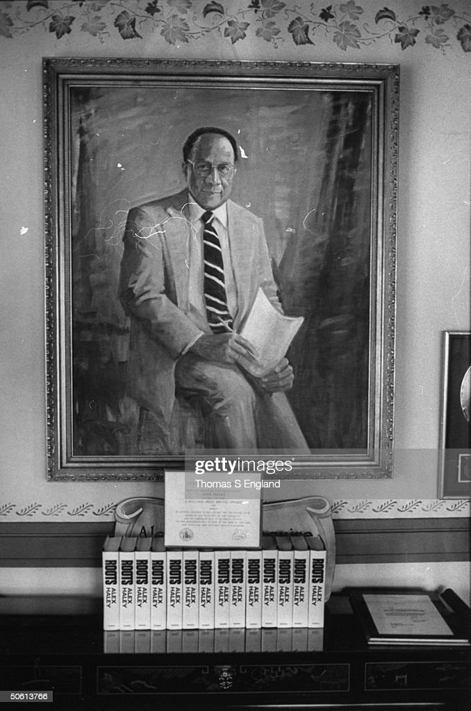 Large portrait ptg of the late author Alex Haley on wall over a display of 14 copies of his book ROOTS a copy of his Pulitzer Prize certificate these...